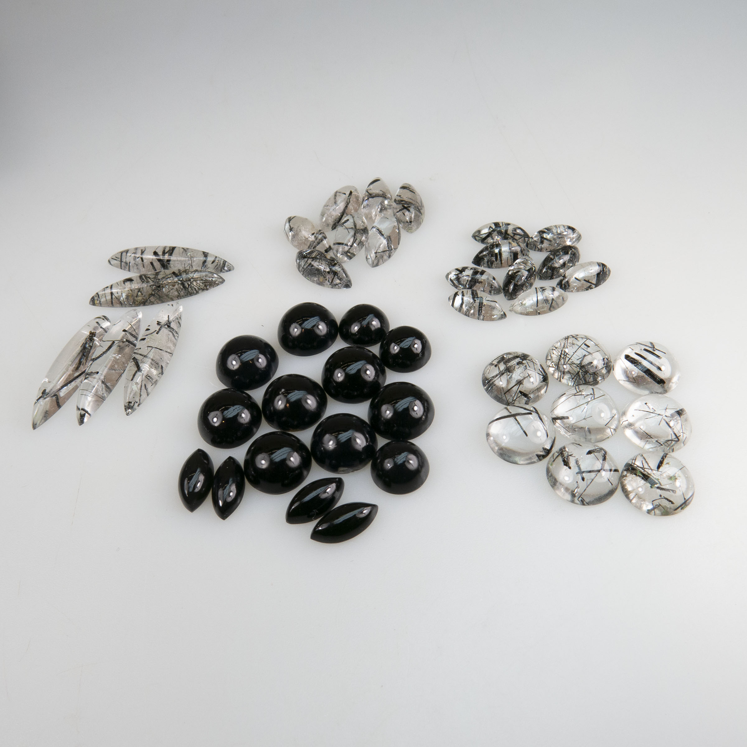 A Collection Of Onyx And Tourmalinated Quartz Cabochons