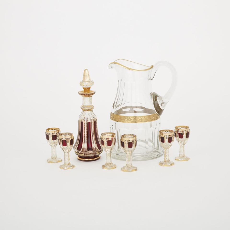 Bohemian Red and Gilt Decorated Cut Glass Decanter and Six Liqueur Glasses, together with a Water Jug, possibly Moser, late 19th/early 20th century